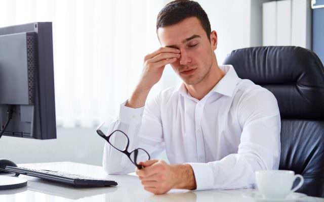 Office Eye Syndrom Augentropfen Brille trockene Augen junger Mann muede